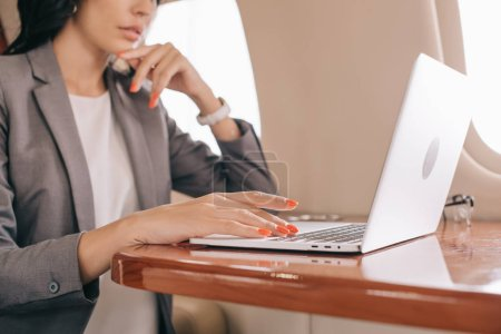 Photo for Cropped view of businesswoman using laptop in private jet - Royalty Free Image