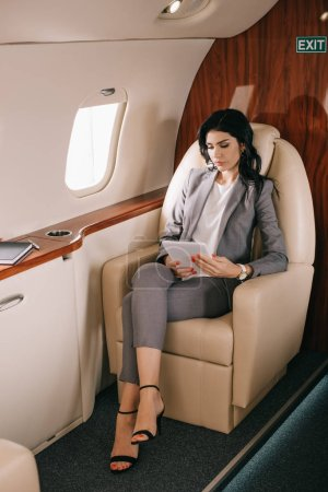Photo for Attractive businesswoman looking at digital tablet in private jet - Royalty Free Image