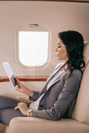 Photo pour Side view of attractive business woman using digital tablet in private jet - image libre de droit