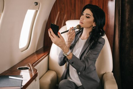 Photo for Selective focus of attractive businesswoman holding cosmetic brush near face in private jet - Royalty Free Image