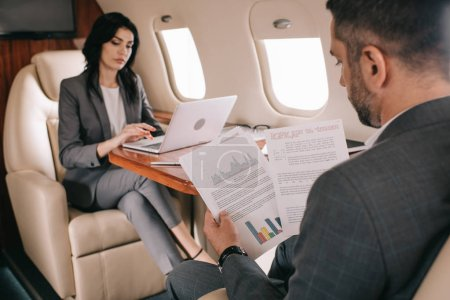 Photo for Selective focus of bearded businessman holding charts and graphs near attractive businesswoman using laptop in plane - Royalty Free Image