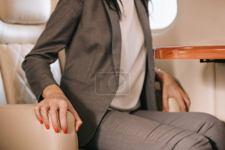 Photo for Cropped view of businesswoman with flight fear sitting in private jet - Royalty Free Image