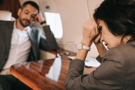 Photo for Selective focus of stressed woman with fear of fright sitting with businessman in private jet - Royalty Free Image