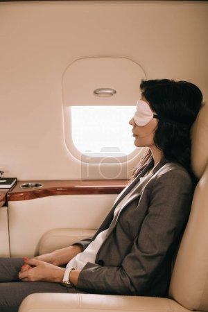 Photo pour Vue latérale d'un homme d'affaires en masque endormi assis près de la fenêtre d'un avion à réaction privé - image libre de droit