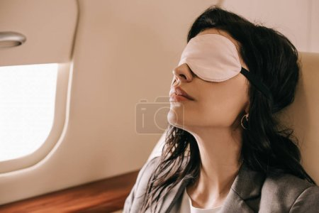 Photo for Businesswoman in sleeping mask sitting in private jet - Royalty Free Image