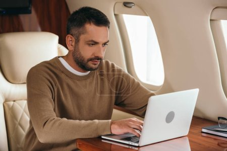 Photo for Handsome bearded man using laptop in private jet - Royalty Free Image