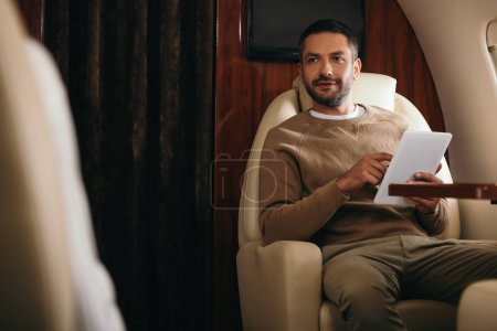Photo for Selective focus of handsome bearded man using digital tablet in private jet - Royalty Free Image