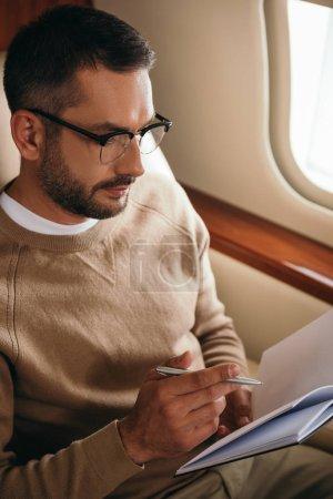 Photo pour Bel homme barbu dans des lunettes regardant cahier tout en tenant stylo en jet privé - image libre de droit