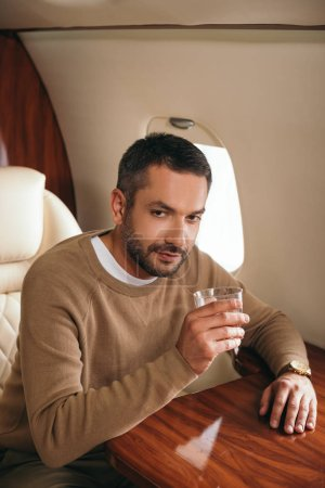 Photo for Handsome bearded man holding glass with alcohol drink while sitting in first class of private jet - Royalty Free Image