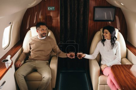 Photo for Happy man and woman clinking glasses in private jet - Royalty Free Image