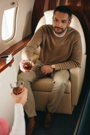 Photo for Cropped view of woman clinking glasses with handsome man in private jet - Royalty Free Image