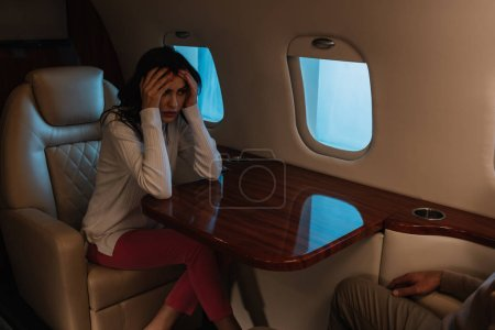 Photo for Cropped view of man sitting near scared woman with fear of flight in private jet - Royalty Free Image