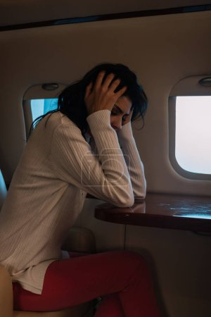 Photo for Scared woman with airsickness touching hair in private jet - Royalty Free Image