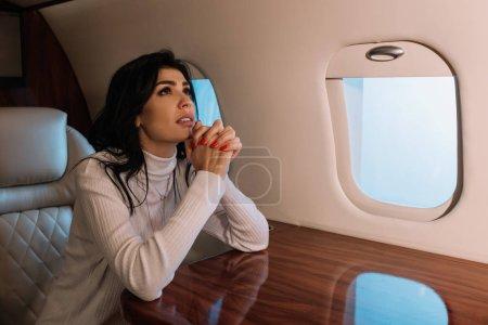 Photo pour Femme effrayée assis avec des mains priantes en jet privé - image libre de droit