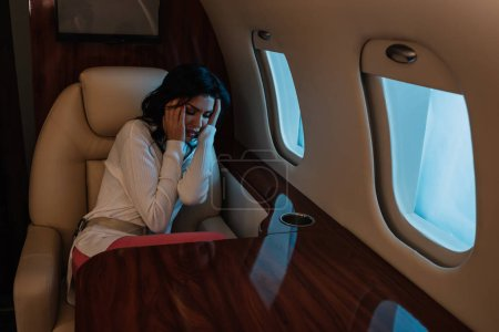 Photo for Scared woman with airsickness touching hair while sitting in private jet - Royalty Free Image