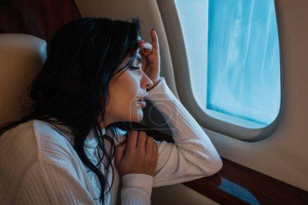 Photo pour Femme effrayée avec le mal de l'air regardant la fenêtre de l'avion en jet privé - image libre de droit