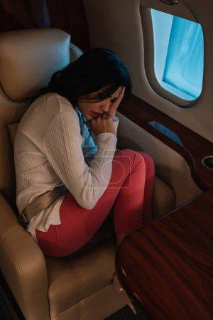 Photo pour Vue aérienne de la femme effrayée avec le mal de l'air assis en jet privé - image libre de droit
