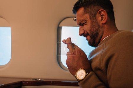 Foto de Hombre asustado con los ojos cerrados y los dedos cruzados en chorro privado - Imagen libre de derechos