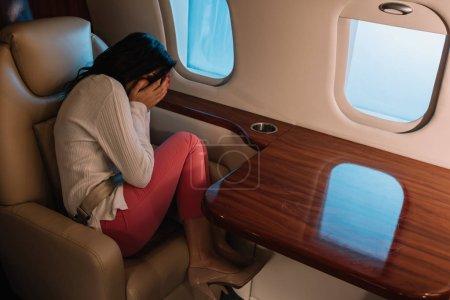 Photo pour Femme effrayée avec le visage de couverture de mal de l'air tout en étant assis dans un jet privé - image libre de droit