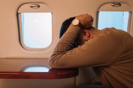 Photo pour Homme effrayé avec le visage de couverture de mal de l'air en jet privé - image libre de droit