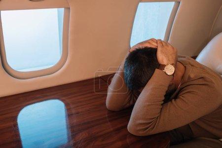 Photo pour Homme effrayé avec le mal de l'air couvrant visage en jet privé - image libre de droit
