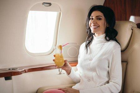Photo pour Femme gaie tenant cocktail savoureux en jet privé - image libre de droit