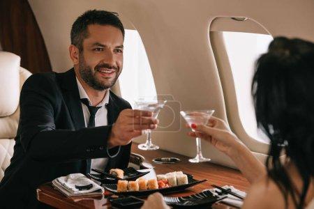 Photo pour Crochet vue d'une femme tenant des lunettes de martini près d'un homme heureux à bord d'un avion privé - image libre de droit