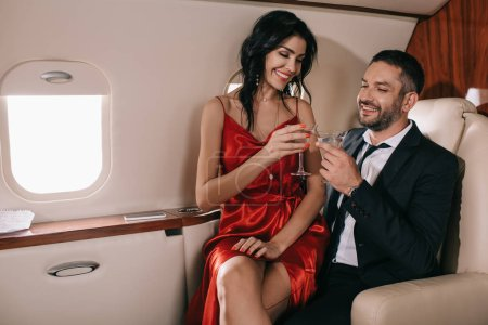 Photo pour Heureux couple tenant des lunettes de martini en jet privé - image libre de droit