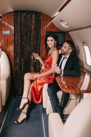 Photo for Selective focus of happy couple holding martini glasses in private jet - Royalty Free Image