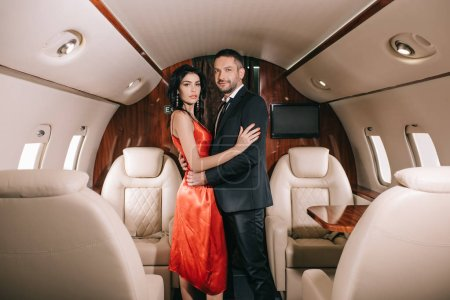Photo pour Attractive woman in red dress standing with handsome bearded man in private jet - image libre de droit