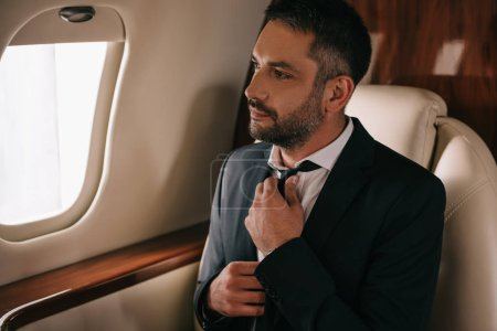 Photo for Bearded businessman touching tie and sitting in plane - Royalty Free Image