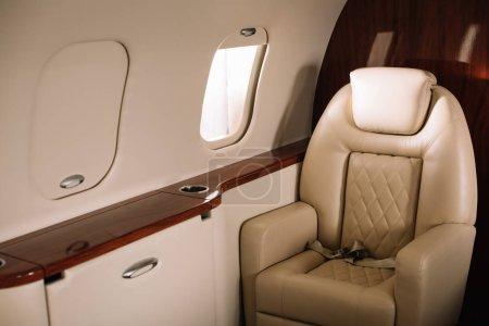 Photo pour Lumière du soleil sur le siège en cuir près de la fenêtre de l'avion en jet privé - image libre de droit