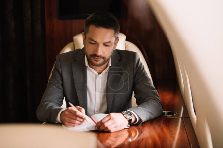 selective focus of bearded businessman holding pen while writing in notebook and sitting in plane