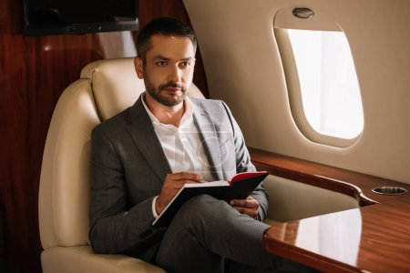 Photo for Selective focus of bearded businessman holding notebook and pen in private jet - Royalty Free Image