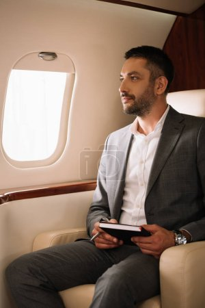 handsome bearded businessman holding notebook and pen in private jet