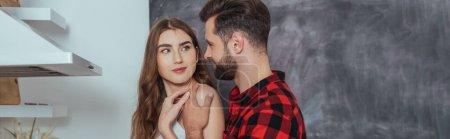 panoramic shot of young man touching shoulder of smiling girlfriend