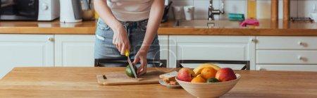 abgeschnittene Ansicht eines Mädchens, das Avocado in der Nähe einer Schüssel mit frischen Früchten schneidet, horizontales Bild