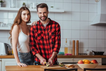 happy young couple smiling at camera while preparing breakfast with fresh fruits together