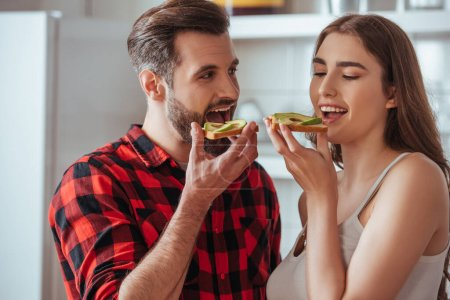 cheerful young couple holding toasts with fresh avocado