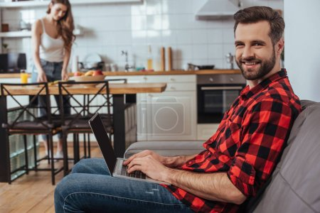 Photo for Selective focus of handsome freelancer smiling at camera while working on laptop in kitchen near girlfriend on background - Royalty Free Image