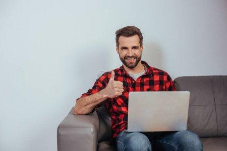 Photo pour Heureux freelance souriant à la caméra et montrant pouce vers le haut tout en étant assis sur le canapé avec ordinateur portable - image libre de droit