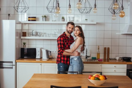 Photo for Happy young couple embracing and looking at camera while standing in modern kitchen - Royalty Free Image