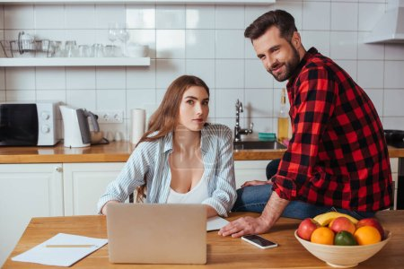 smiling man looking at camera while sitting on table near busy girlfriend working on laptop