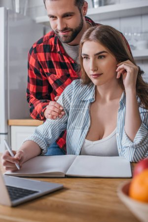 Photo for Smiling man touching shoulders of attractive freelancer looking at laptop and writing in notebook - Royalty Free Image