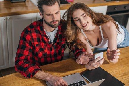 Photo pour Fille gaie montrant smartphone occupé, petit ami sérieux assis à la table de cuisine et travaillant sur ordinateur portable - image libre de droit