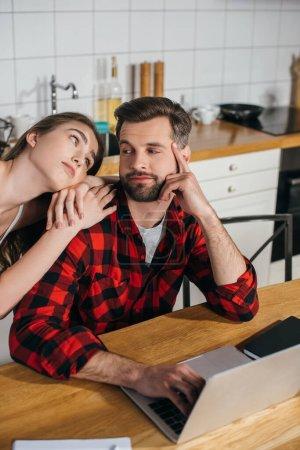 Photo pour Fille ennuyée s'appuyant sur l'épaule du copain occupé assis à la table de cuisine et travaillant sur ordinateur portable - image libre de droit