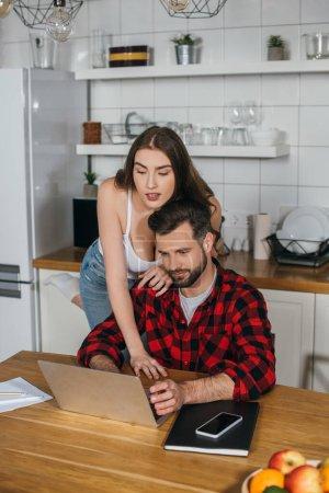 Photo pour Jolie fille appuyé sur l'épaule de copain occupé assis à la table de cuisine et travaillant sur ordinateur portable - image libre de droit