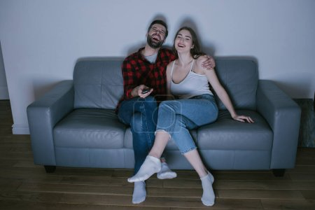 Photo for Cheerful couple laughing while watching tv on sofa at home - Royalty Free Image