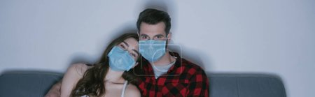 Photo for Horizontal image of young couple in medical masks watching tv on sofa at home - Royalty Free Image