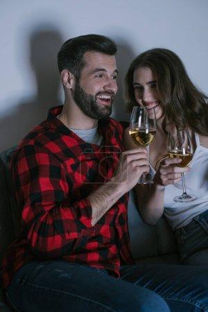 Photo pour Heureux jeune couple riant tout en étant assis sur le canapé et tenant des verres de vin blanc - image libre de droit
